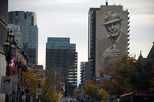 A mural of musician Leonard Cohen is seen on a building on November 7, 2017 in downtown Montreal. Leonard Cohen's songs strived for the universal and his voice was often solemn, yet the courtly songwriter had plentiful moments of joy and deadpan humor. One year after Cohen died at age 82, an array of artists testified to his far-reaching impact with a concert the evening on November 6, 2017 whose somber yet graceful tone befitted the celebrated singer and poet. Before more than 21,000 people at the Bell Centre arena in Cohen's native Montreal, the tribute built around short videos of his well-traveled life which included years of artistic retreat on the Greek island of Hydra and a late-age stint as a Buddhist monk in California. / AFP PHOTO / Marc BRAIBANT